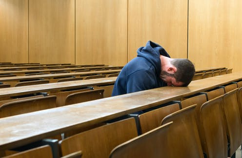 Lone student in lecture theatre with head on desk