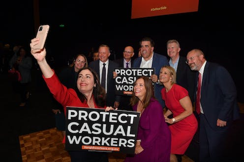 "Terri Butler takes a selfie with Anthony Albanese, and several others, carrying signs which read ""Protect Casual Workers"""