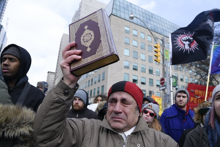 A Muslim man at a rally holding up a copy of the Quran and crying