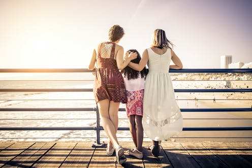 Two women with their daughter looking over a bridge.