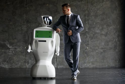 A man in a suit leans casually on the shoulder of a basic-looking robot