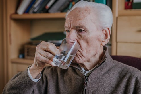 A man taking a tablet with water