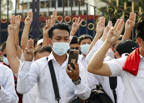 Group of young men and women in white shorts and COVID masks with their left hands using three-fingered protest salute from The Hunger Games.
