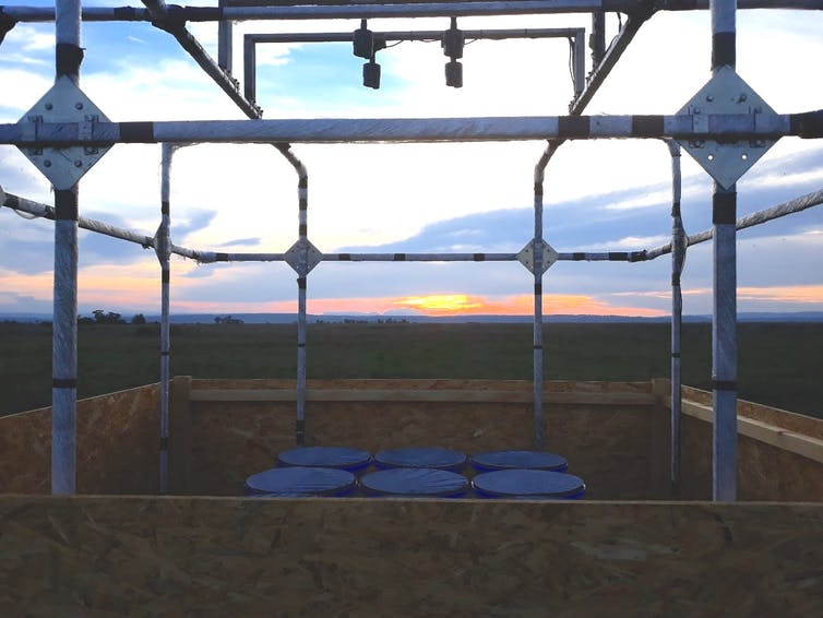 A scaffold structure set up in a field at sunset