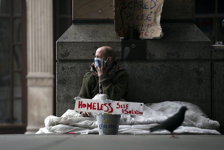 A homeless man wearing a mask