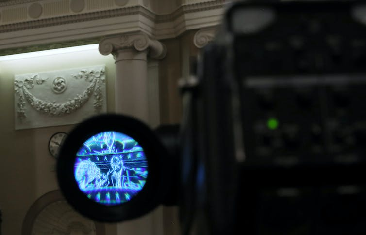 A congressman on the House floor is shown through the lens of a camera.