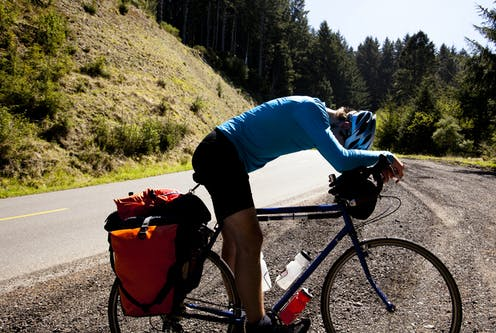 A tired cyclist leaning over their bike