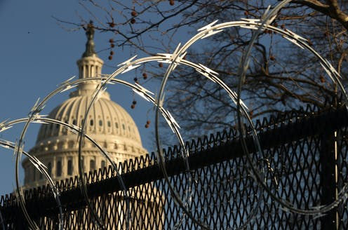 The US Capitol dome, behind a security fence topped with razor wire