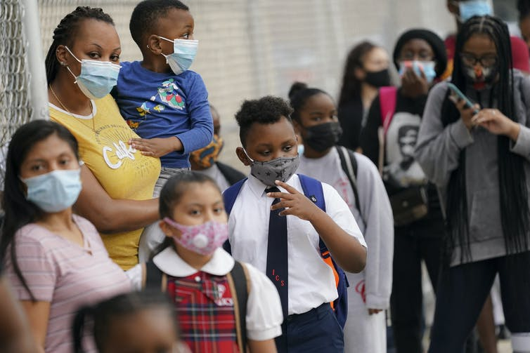 Children and parents wait outside a New York City school wearing masks.