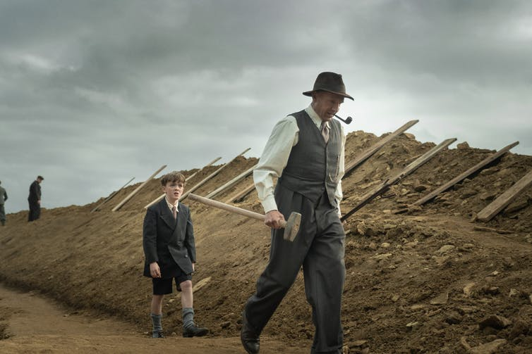 Film still. Basil holds a mallet and walks past a mound of dirt. He is followed by a young boy.