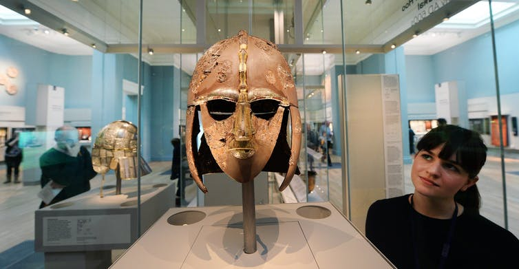 A woman looks at the Sutton Hoo helmet at the British Museum
