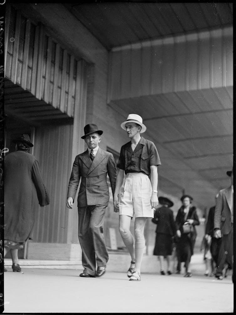 Two men walk down street in fashion suits of 1930s.