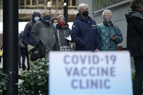 People wearing masks waiting in line to receive a COVID-19 vaccine