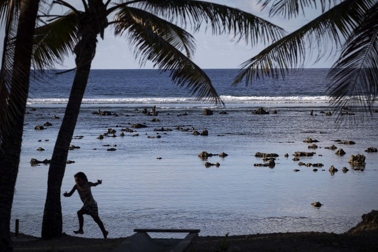 A child plays on a beach in Nauru.