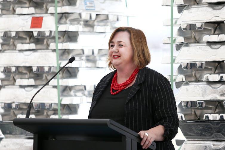 Megan Woods speaking in front of aluminium ingots.