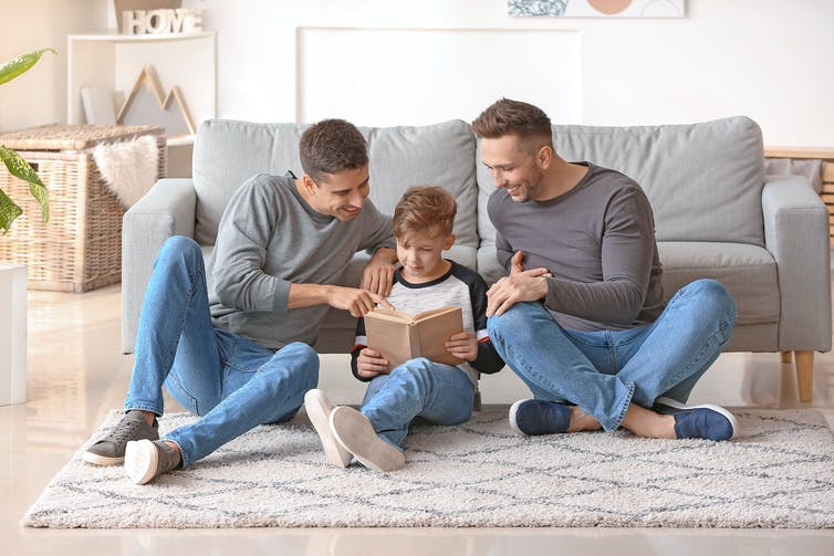 Two fathers reading with their son.