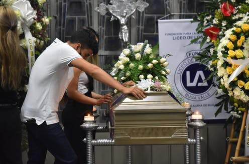 Man in white t-shirt leans on a coffin with flower displays at a church in Buga, Valle del Cauca, Colombia.