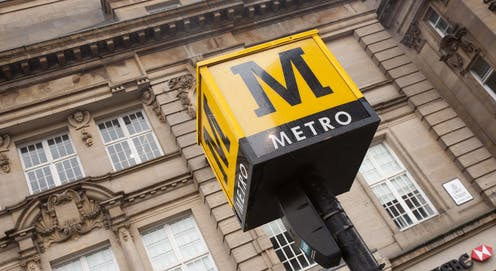 Yellow metro sign in front of city building