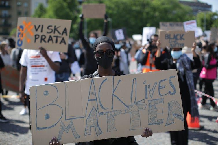 A protestor hold up a sign reading 'Black Lives Matter' at a protest in Gothenburg, Sweden.