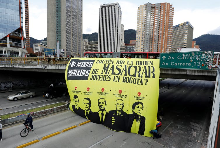 A view of a poster that reads 'Who gave the order to massacre youth in Bogota?' hanging from a bridge over a highway in Bogota, Colombia.