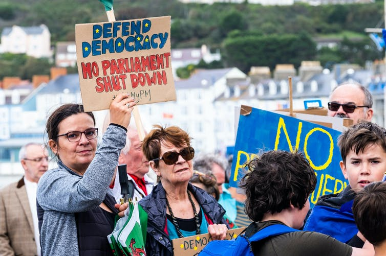 A woman at a 2019 protest again parliamentary prorogation holds a sign reading 'defend democracy, no parliament shut down'.