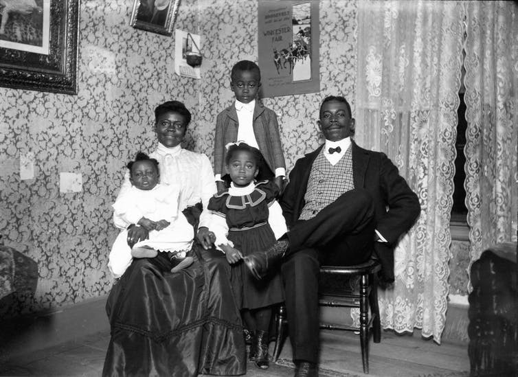 The family, proudly dressed, is photographed indoors, in front of lace curtains and framed prints.