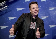Elon Musk's left and right hands express a thumbs up gesture.