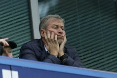Roman Abramovich rests his hands on his face as he watches his Chelsea soccer team play.