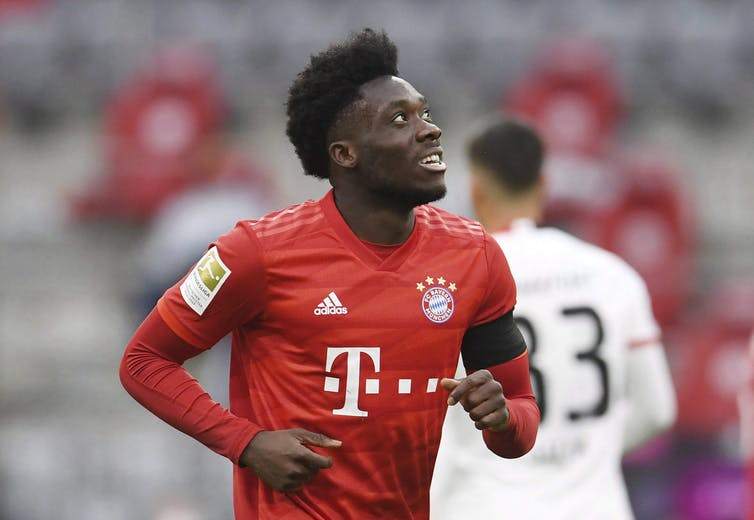 Alphonso Davies runs on the pitch in red kit