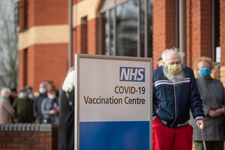 People queue at a COVID-19 vaccination centre in the United Kingdom.