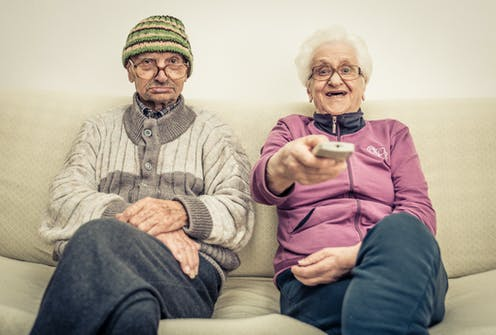 old couple watching television on the couch