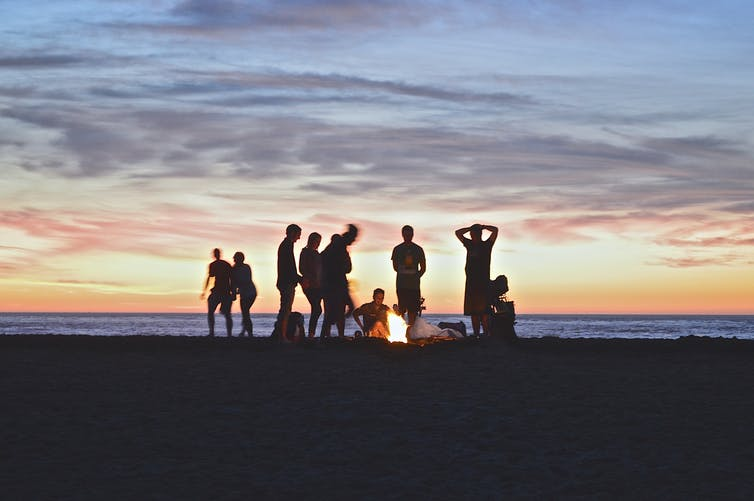 Silhouettes of young people on a beach, in the evening around a fire.