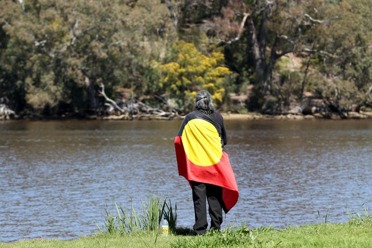 Man wrapped in Aboriginal flag stands on river bank.
