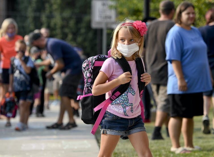 Children head to school past adults not wearing masks