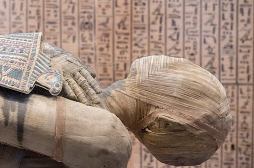 Close up of an Egyptian mummy with hieroglyphics in the background.