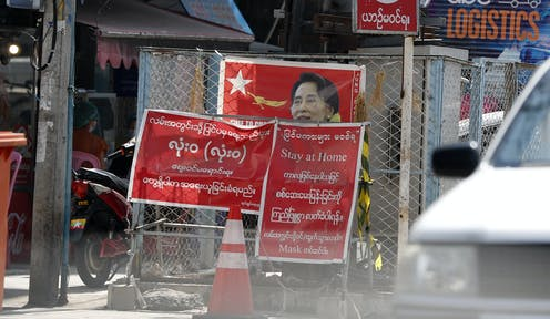 Signs in Burmese and ENglish telling people to stay at home obscure an NLD election poster.