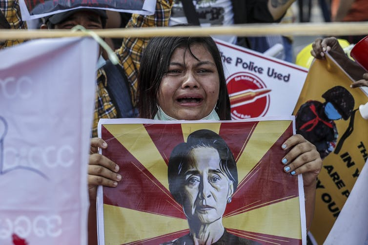 A Burmese woman holding up a poster of NLD leader Aung San Suu Kyi.