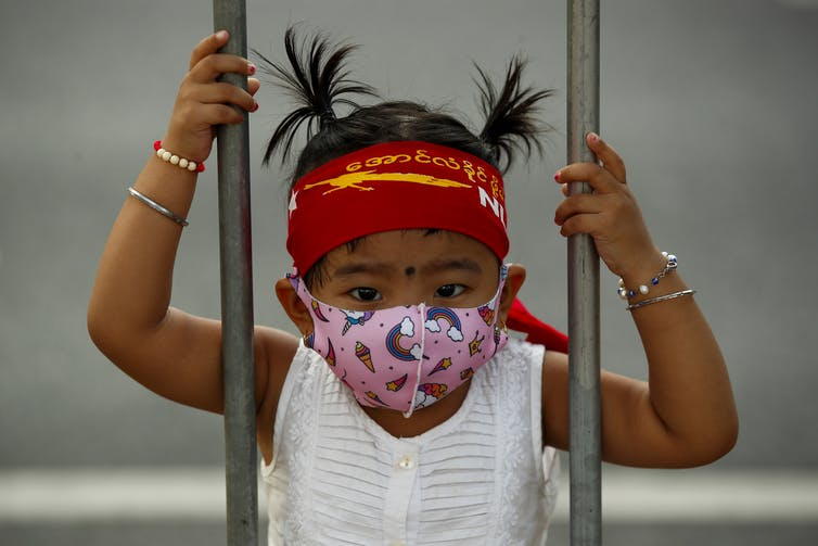 Young girl in a COVID mask and an NLD headband between two bars.