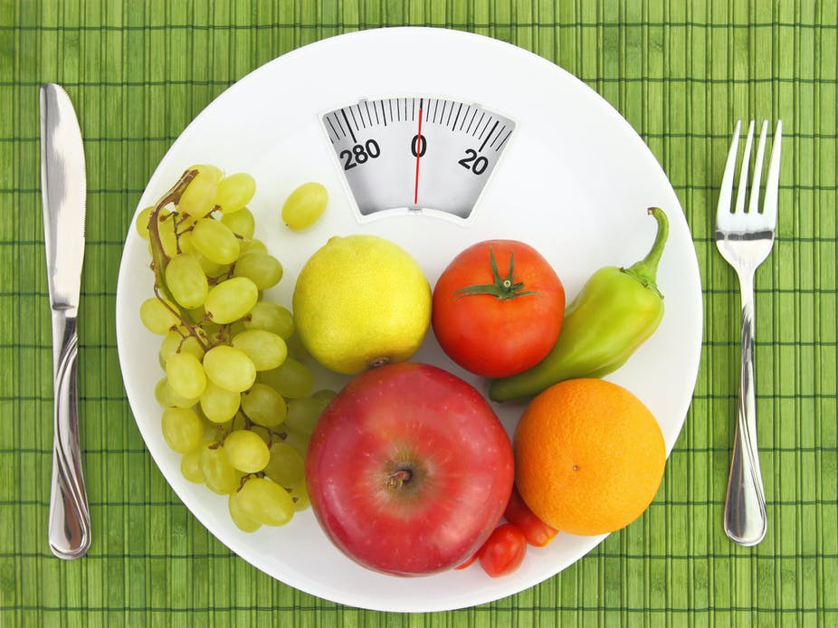 Healthy fruits and vegetables on a scale with a knife and fork on either side.