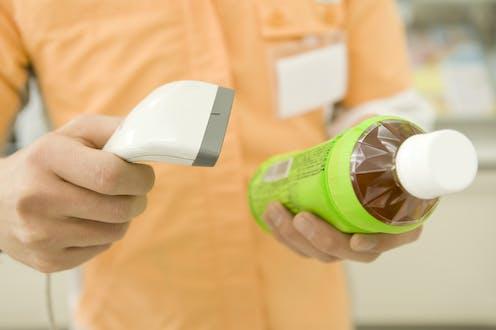 A shop clerk scans a plastic bottle.