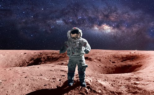 An astronaut in a space suit standing on Mars, with the Milky Way in the background.