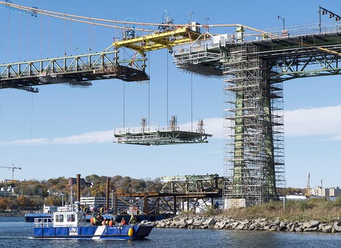 Workers lift a new portion of a bridge.