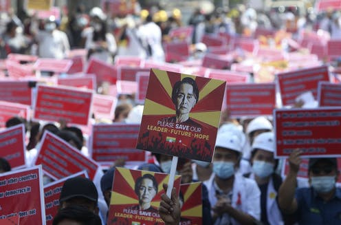 A protester holds up a placard with an image of deposed Myanmar leader Aung San Suu Kyi during an anti-coup rally with many signs seen in the background.