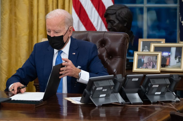 President Biden signing an executive order at his desk