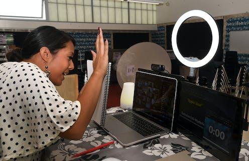 A teacher waves 'hello' to her online class.