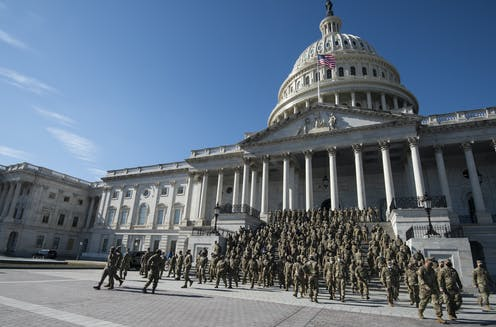 Zoomed out image of Capitol with dozens or hundreds of soldiers in camoflauge descending steps