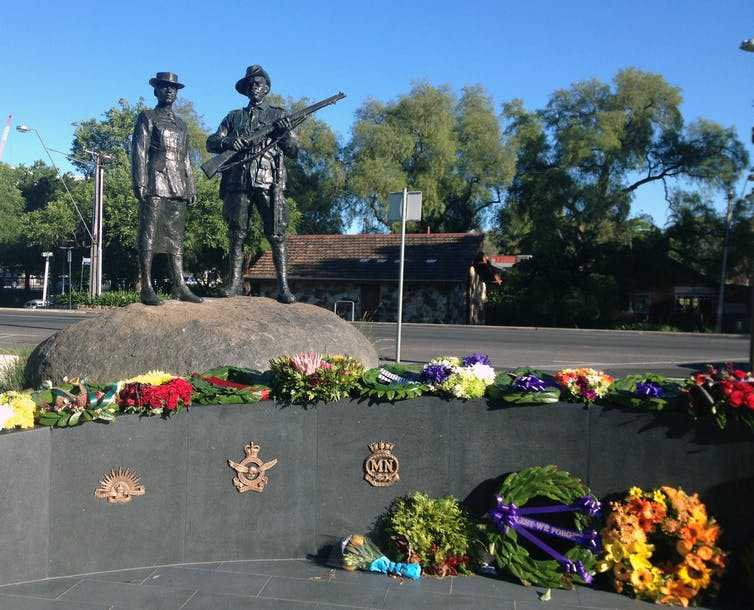 A statue of two soldiers, surrounded by wreaths.