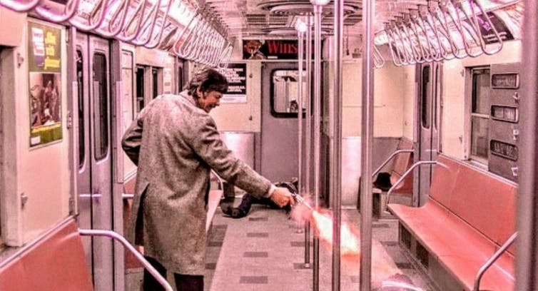 A man shoots a gun on the subway.