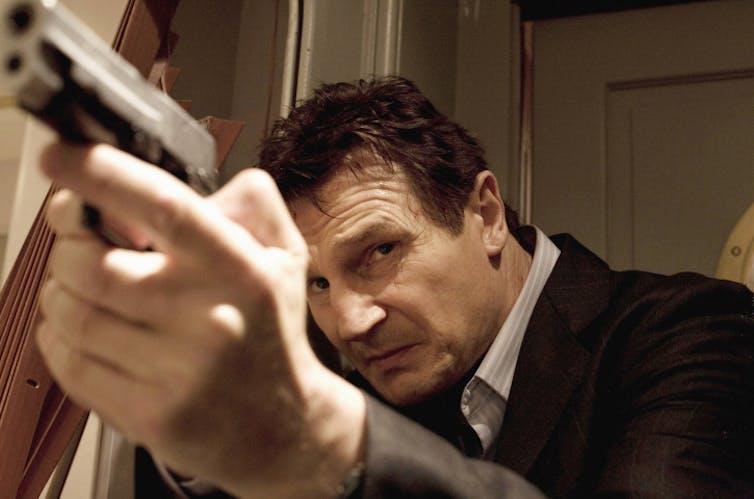 Neeson aims a gun.