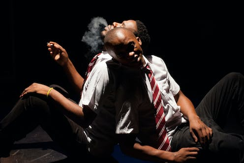 Lit up in the dark, two men sit, leaning their backs against one another, one exhaling a plume of smoke from a hand-rolled cigarette.